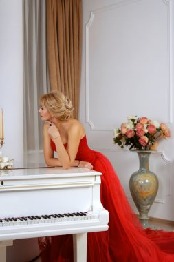 A woman dressed in red long dress leaning over white piano in th