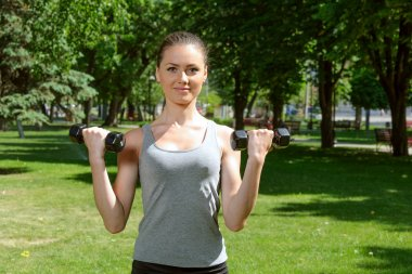 Sports girl makes exercises with dumbbells