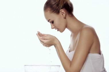 Girl washes her face, leaning over a bowl, and with her hands dr