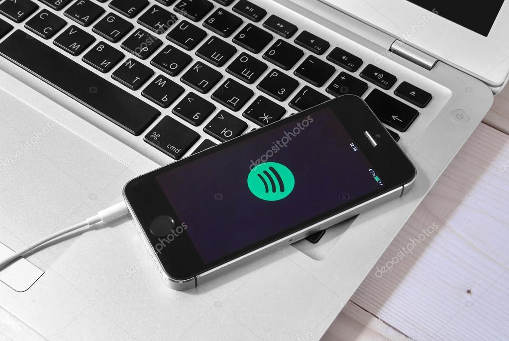iPhone 5s on laptop with mobile application for Spotify on the s