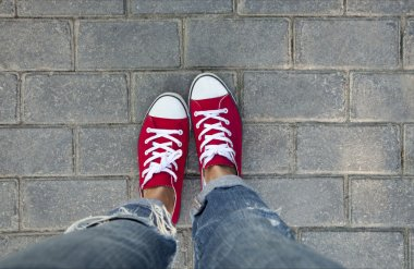 women's feet in red sneakers
