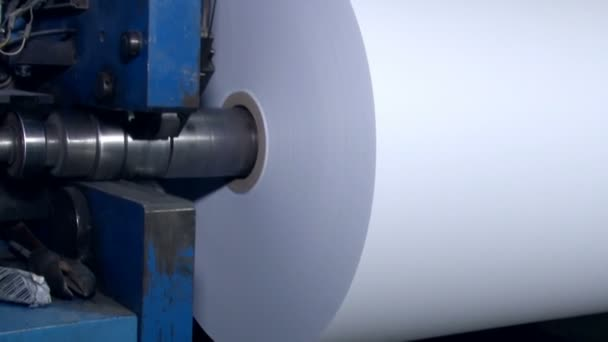 A wide paper roll is rotated on the machine for further cuts