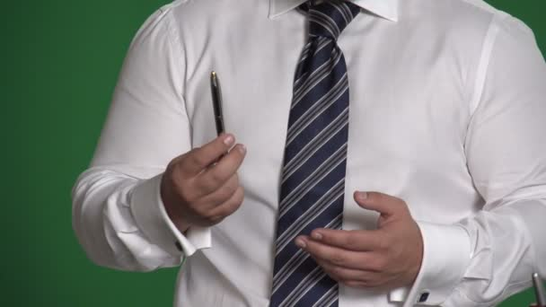 Gesture male hand with a pen on a green background 2