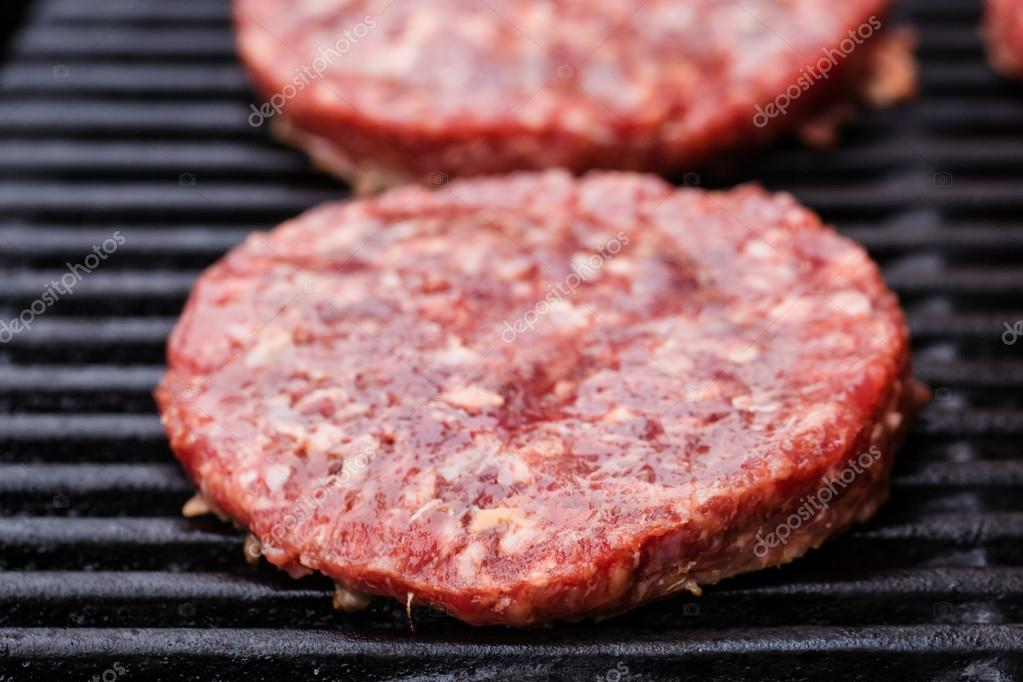 Preparing a batch of  grilled ground beef patties or frikadeller on BBQ