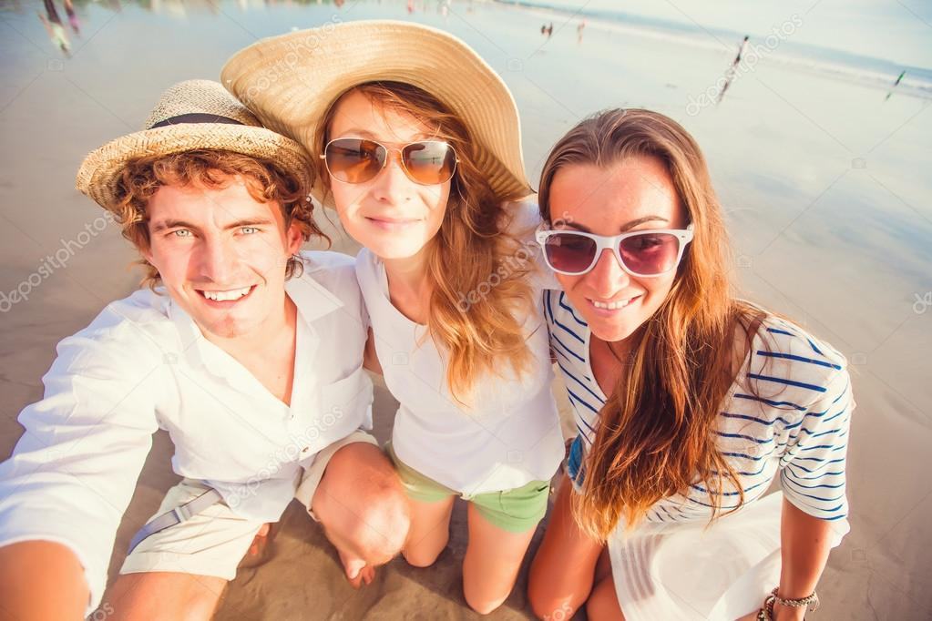 Group of happy young people taking selfie on the beach