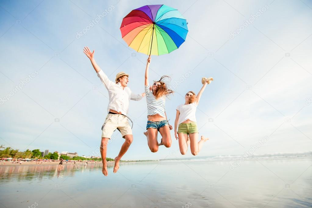 Group of happy young people having fun on the beach