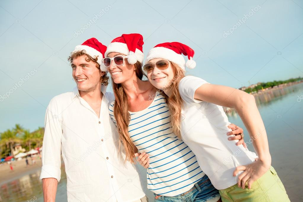 Group of happy young people in christmass hats on the beach