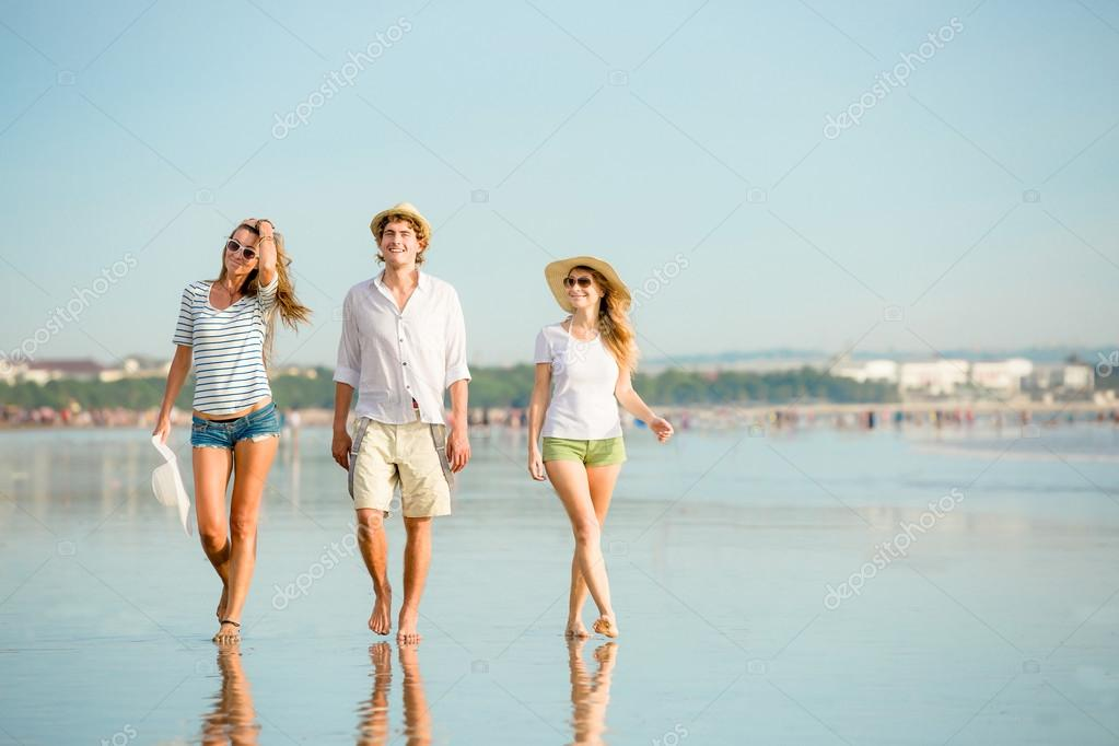 Group of happy young people walking along the beach on beautiful summer sunset