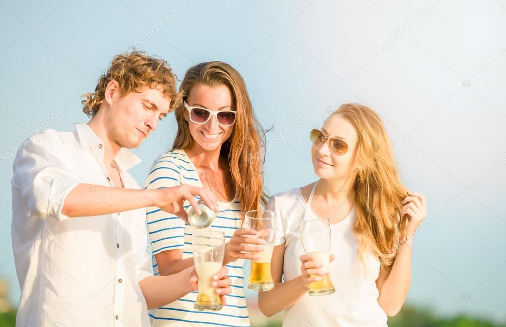 Group of happy young people drinking beer on the beach