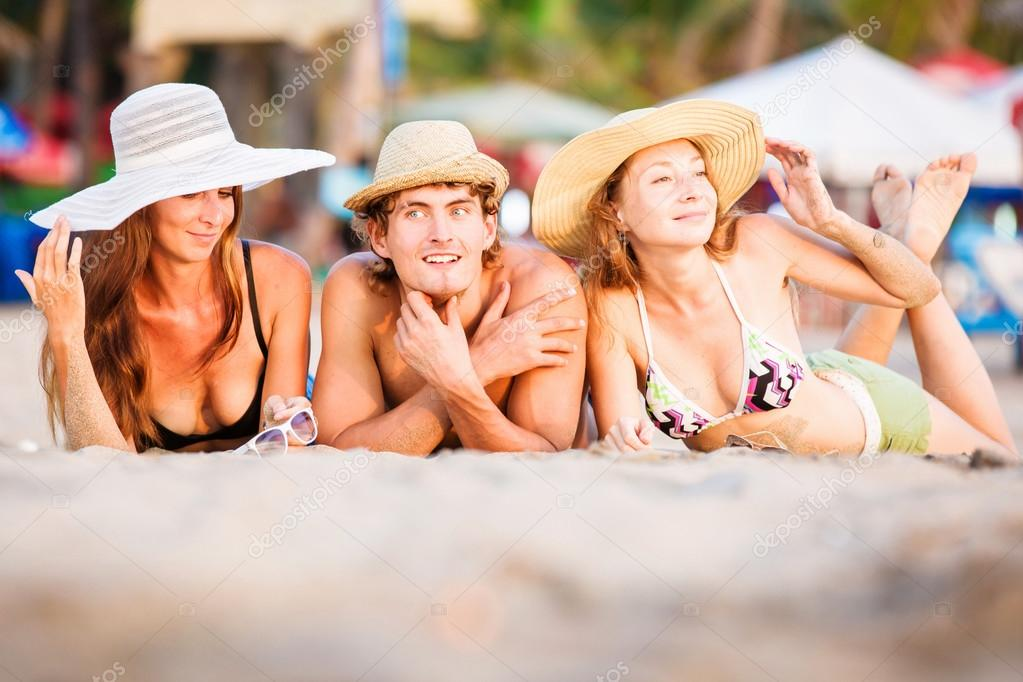 Group of happy young people lying on wite beach sand