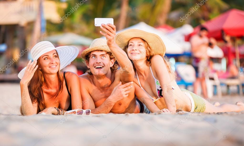 Group of happy young people lying on wite beach sand and taking selfie photo