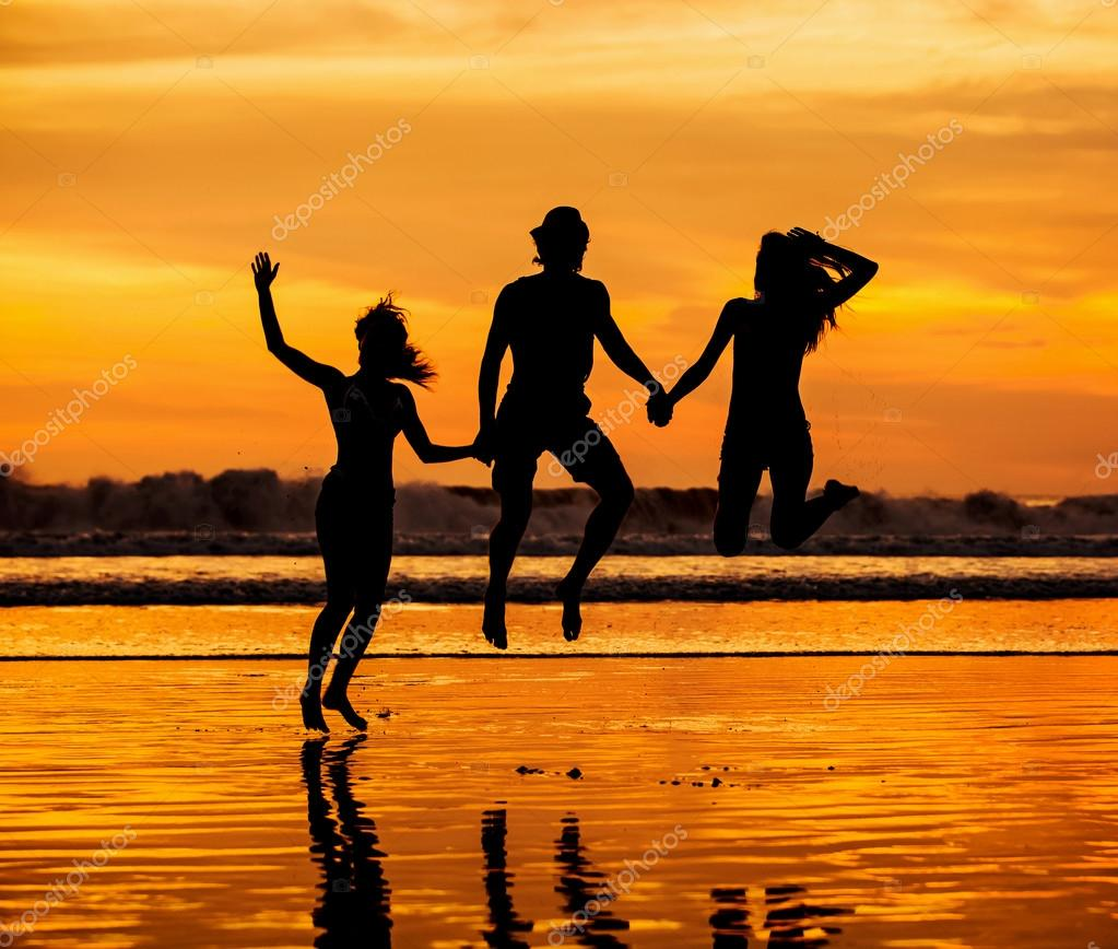 Silhouettes of happy young friends jumping on the beach  against red sunset