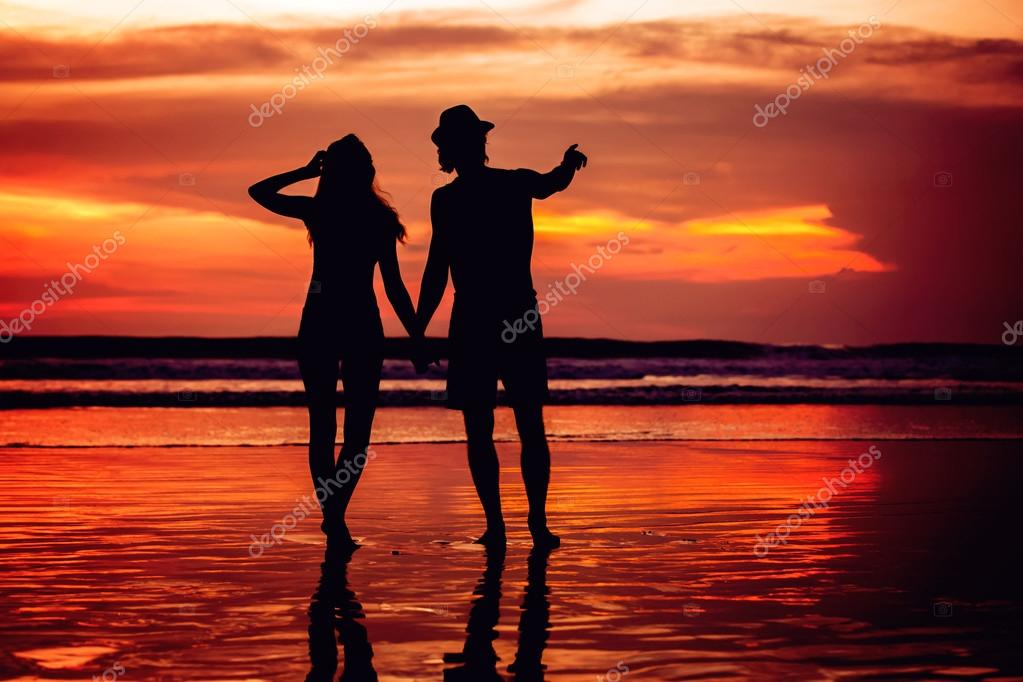 Silhouettes of young couple in love staing on the beach with beautiful red sunset as background