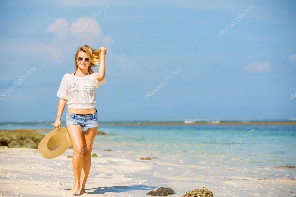 Young skinny caucasian girl at the beach with blue sky on background. Travel, vacation, paradise concept, copyspace