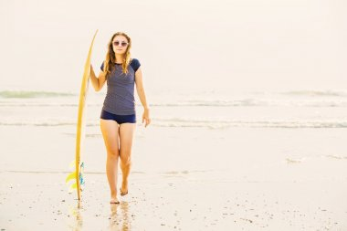 Beautiful young surfer girl stays on the beach at sunset with yellow surfboard. Healthy lifestyle, leisure, travel, holiday and sport concept, copyspace
