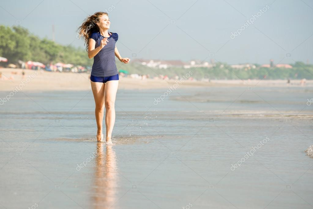 Healthy woman running on the beach, girl doing sport outdoor, happy female exercising, fitness and heath care concept with copy space over natural warm sunset background