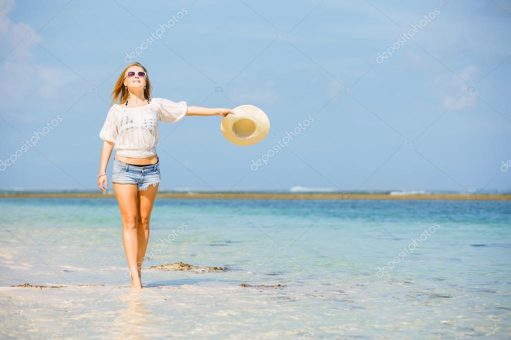Young skinny caucasian girl at the beach waving with white hat over blue sky and pure ocean water on background. Travel, vacation, paradise concept, copyspace