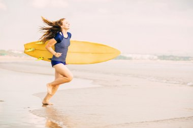 Beautiful sexy surfer girl on the beach at sunset running into ocean, yellow surfboard in her hands. Healthy life, sport  concept with copyspace