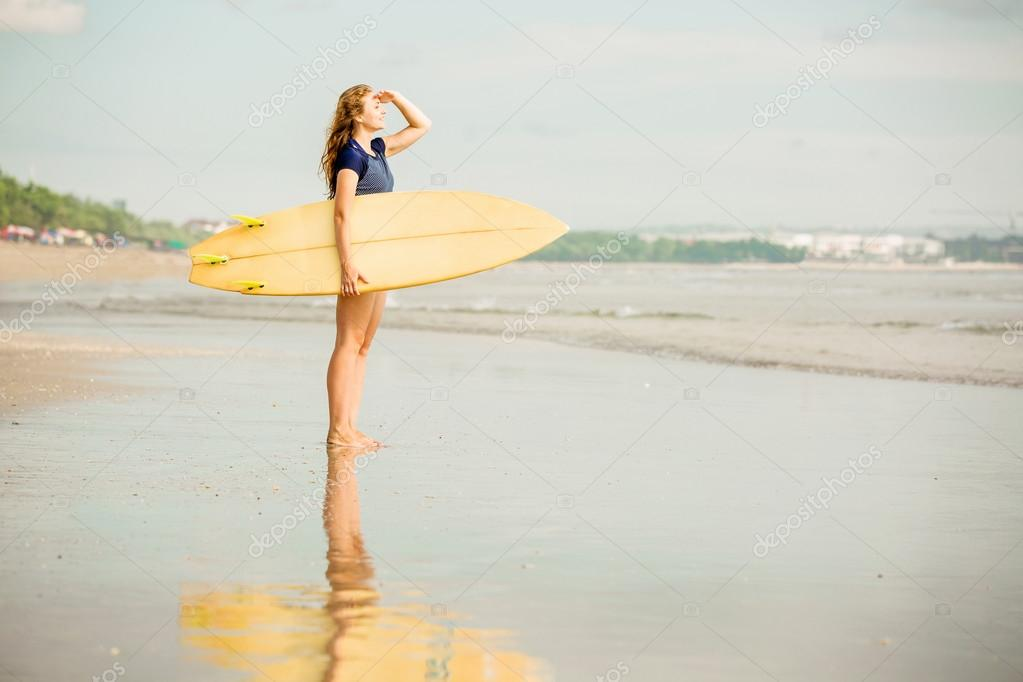 Beautiful sexy surfer girl on the beach at sunset looking for waves from shore with surfboard in her hands