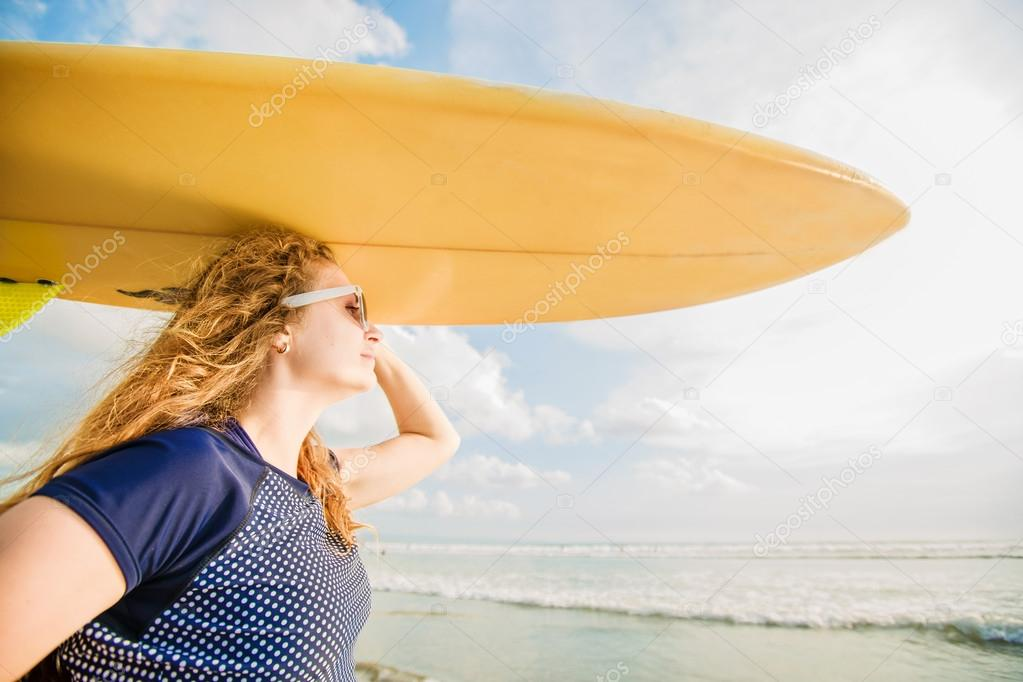 Beautiful young caucasian girl in rushwest and sunglasses with yellow surfboard at legian beach, Bali. Lyfestyle, leisure, sport, vacation, happines concept