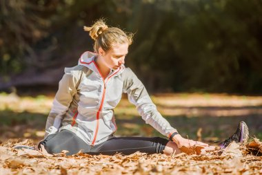Young fit sporty woman stretching before jogging sitting in yellow autumn leaves