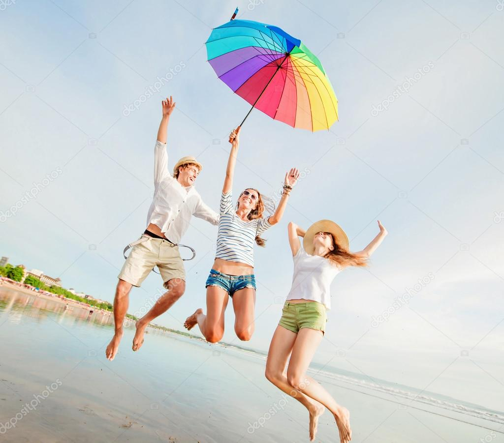 Happy young friends jump with colourful umbrella at the beach on beautiful summer sunset