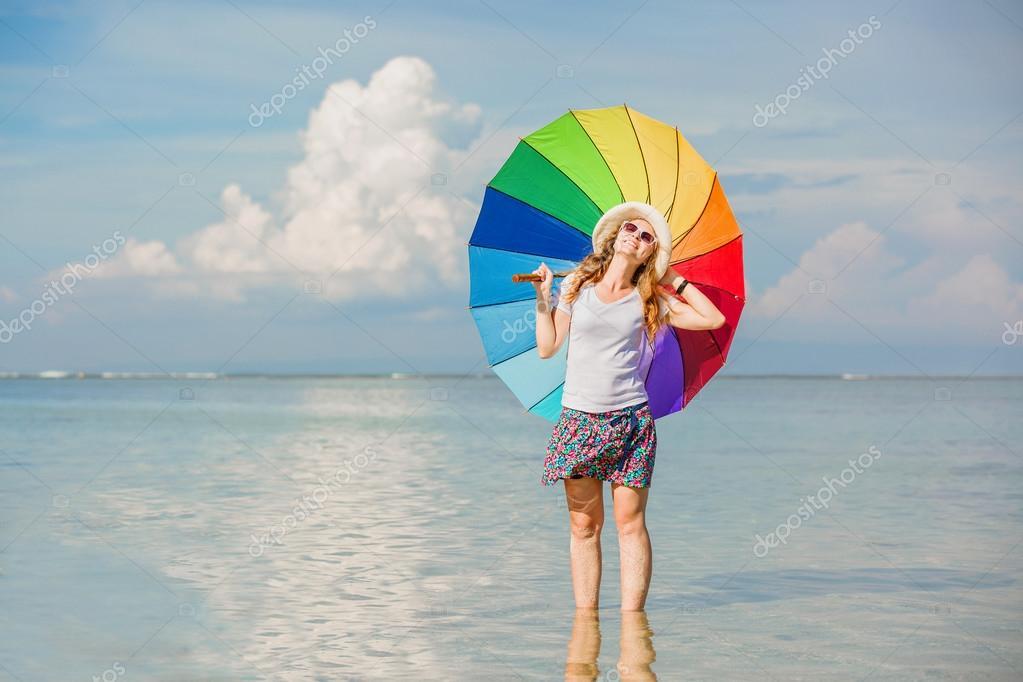 Веселая дама с зонтиком на пляже
