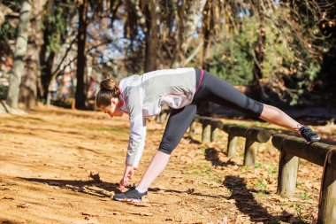 Young fit girl stretching out on bench before exercising in autumn park