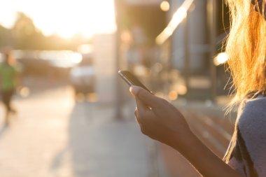 closeup women using smartphone at sunset