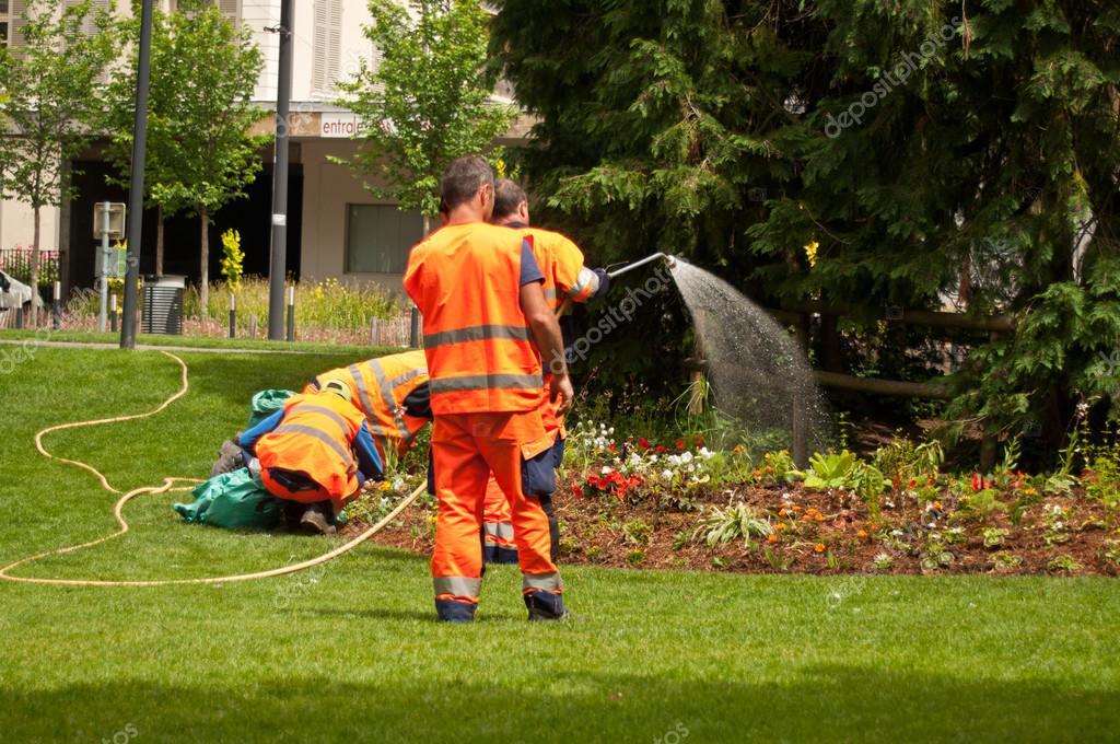 Gardeners watering in public garden