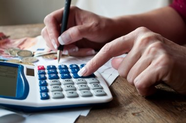 closeup of woman with calculator and money on desk