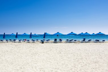 Many beach chairs and umbrellas on white sand sea beach with a blue sky. Concept for rest, relaxation, holidays, spa, resort.