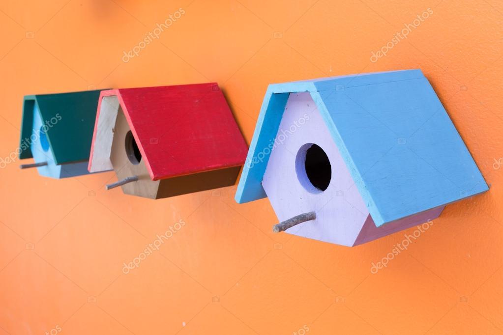Kleurrijke vogel nest hout vak ingericht op oranje muur achtergrond
