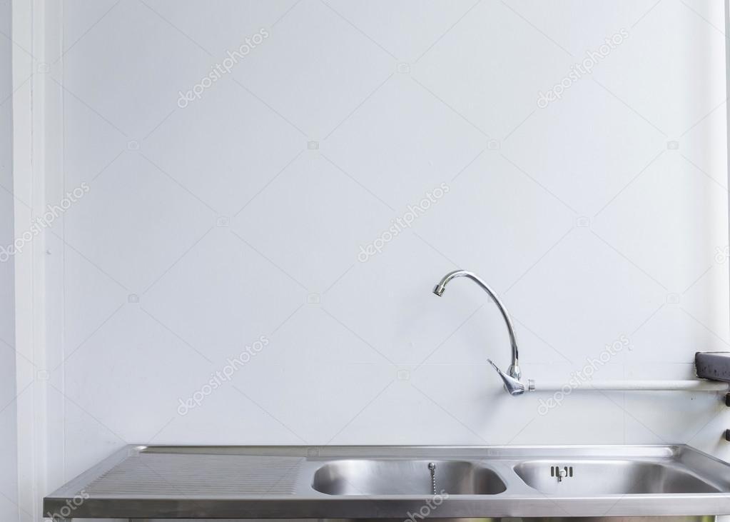 Roestvrij stalen gootsteen en kraan op witte keuken kamer