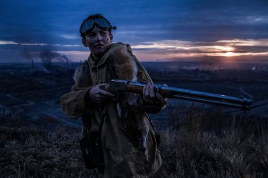 boy stands on a mountain with a gun. a young man with a fox skin on his shoulders. and takes aim from the weapon. teenage forest hunter.