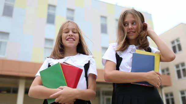 Két csinos tini lány fekete-fehér egyenruhában könyveket tart, mosolyognak és pózolnak az iskolájuk mellett. Lassú mozgás.