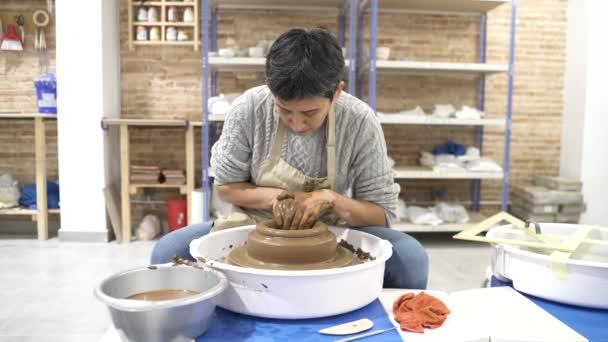 Frau arbeitet mit Ton auf der Töpferscheibe