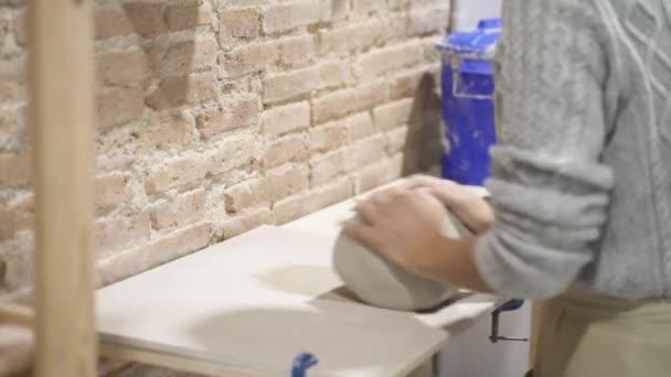 Nahaufnahme einer anonymen Kunsthandwerkerin, die eine Schürze trägt und in der Töpferei Ton vorbereitet.