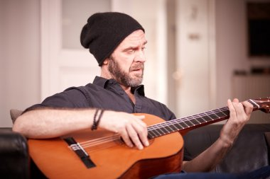 Man with beard playing guitar at home