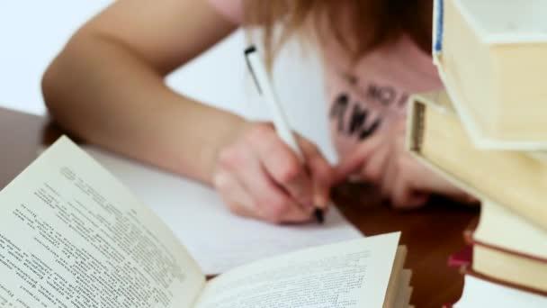 schönes Mädchen am Schreibtisch sitzend. Mädchen bereitet sich auf Prüfungen vor.