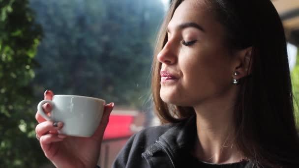 Iszik kávét a kávézóban és mosolyog nagyon szép és vonzó lány.