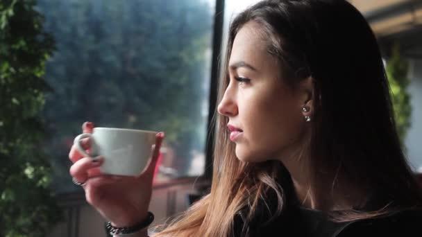 Velmi atraktivní dívka pití kávy v kavárně a úsměvy. Od hrnkem