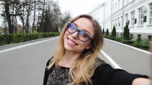 Very Beautiful and Cheerful Girl in the Glasses, Doing Selfie Near the University. Student Hamming and Photographs on Your Phone.