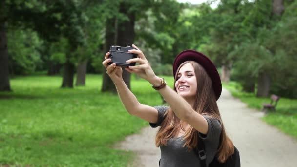 Turistické dívka dělá Selfie na staré filmové kamery. je to velice krásná žena. Má na sobě Red Hat a šedé šaty. Co se týče mnoho zelených stromů