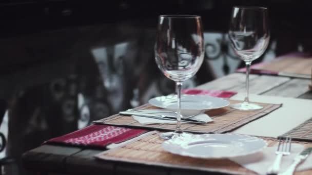 Na stole jsou talíře a brýle. Obsluhované tabulky v ukrajinské restauraci .