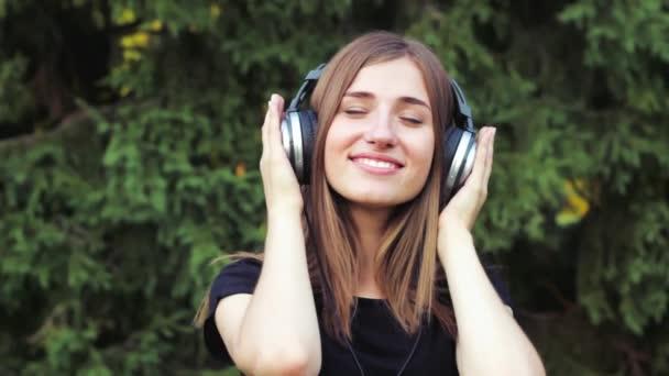 Krásná mladá dívka naslouchající hudbě na sluchátkách. Ta dívka v parku .