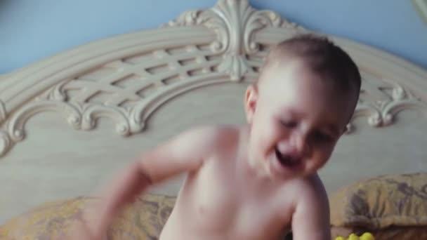 Dítě, smích a hraje v posteli