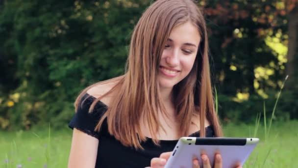 Radostné dívka pracuje na tabletu v sociálních sítích