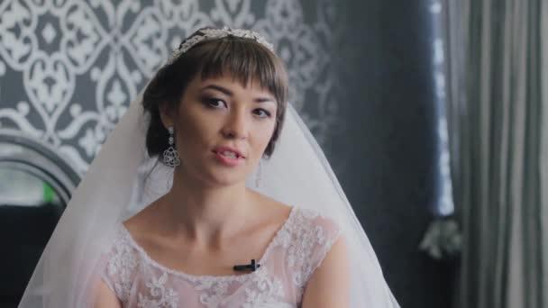 Krásná žena dává rozhovory. Nevěsta v hotelovém pokoji, mluví a při pohledu na fotoaparát