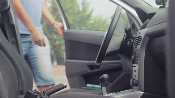 5cf9539a30de2 Le pilote s'asseoir dans la voiture, ferme la porte et s'attache à la  ceinture. Démarrer la voiture. Couleurs métalliques de voiture– séquence  vidéo
